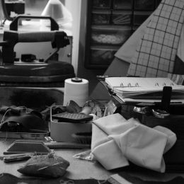 The tailors workbench with the 12lb steam iron, basting thread, pin cushion, press cloth and an array of home made pressing aids.