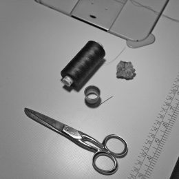 Scissors, needle, thimble, beeswax and sewing thread.