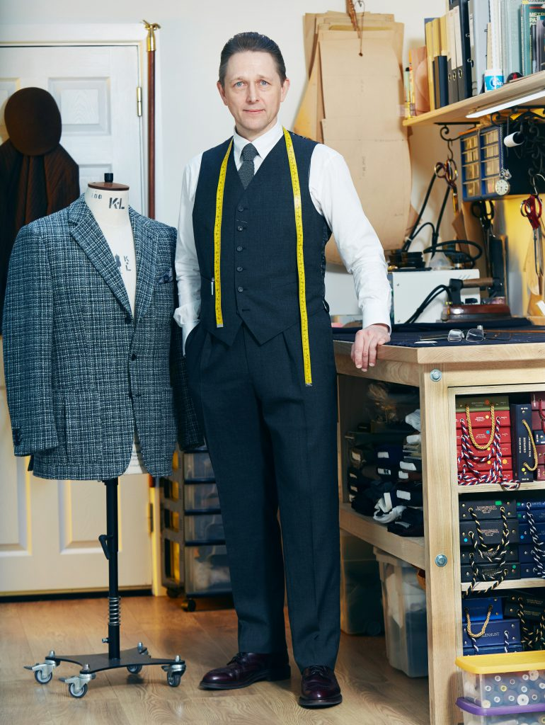 Mark Purcell in his workroom, standing next to a suit jacket